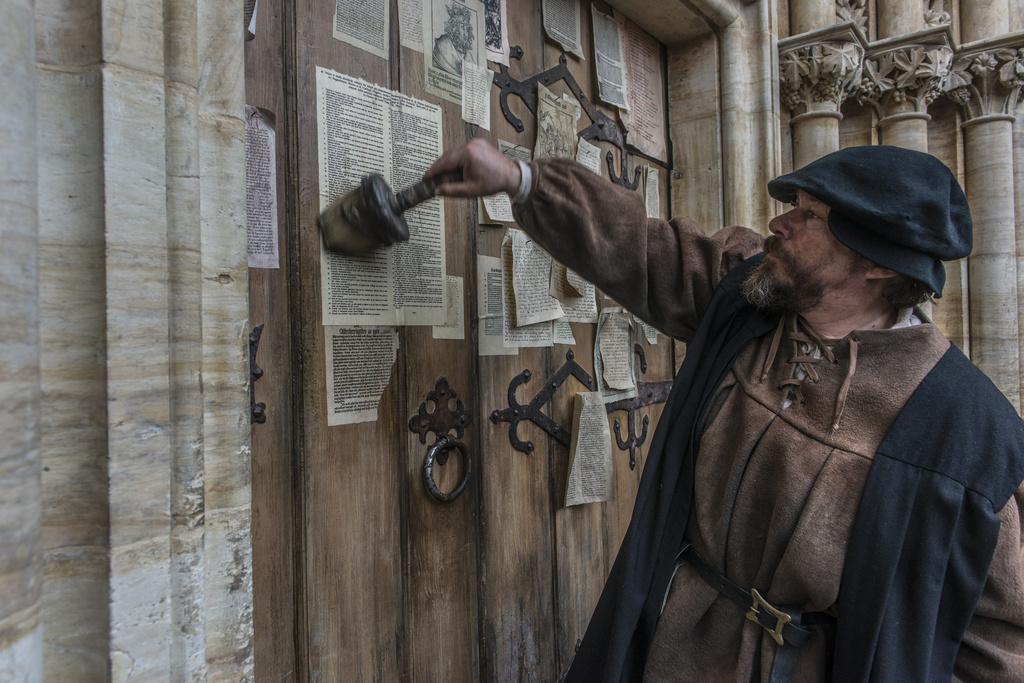 """Luthers Thesen werden an der Schlosskirche zu Wittenberg vom Pedell (Tom Jahn) """"angeschlagen""""."""